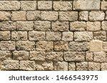 Masonry wall of old stone blocks of limestone. Background texture of ancient brick wall
