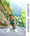 Woman Hiker Climbing Mountain...