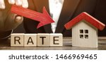 Small photo of Businessman holding the down arrow on wooden blocks with the word Rate and house. Low interest in mortgages. Reducing interest payments for mortgage. The fall in housing rates on credit.