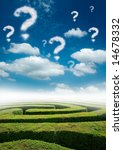 A maze under a blue sky with question mark clouds. - stock photo