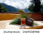 a glass liquor from the swiss stone pine, cones and twigs on a wood table with view to the mountains and of a arolla on a sunny day