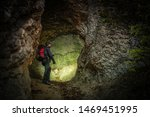 Narrow Cave Expedition. Caucasian Men Exploring Rock Formations. Adventure and Lifestyle Theme. - stock photo