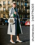 Small photo of PARIS, FRANCE - FEBRUARY 27, 2019: Elisa Nalin wears a trench coat, green dress, and bag with a snake print, seen outside ROCHAS show, during Paris Fashion Week Womenswear Fall/Winter 2