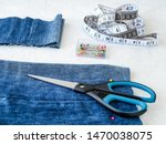 Small photo of Making shorts out of blue jeans with multi colored headed sewing pins, white tailor tape with centimeters and inches and scissors. Shorten the jeans. DIY shorts out of jeans. Top view.