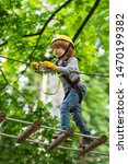 Small photo of Child concept. Rope park - climbing center. Hike and kids concept. Go Ape Adventure. Happy Little child climbing a tree