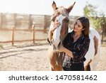 Lovely caucasian woman in checked shirt, hugging horse, horsewoman adore her pet, smiling gently, grooming animal as standing on farm near wooden fence in morning. Girl want become horsewoman