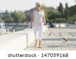 Stock photo senior woman walking her dog 147059168