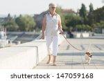 Stock photo senior woman walking her dog 147059168