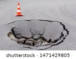 Small photo of Deep sinkhole on a street city and orange traffic cone. Dangerous hole in the asphalt highway. Road with cracks. Bad construction. Damaged asphalt road collapse and fallen.