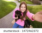 Stock photo young woman taking selfie with adorable brussels griffon dogs outdoors 1472462372