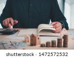 Small photo of Businessmen are using calculators and notebooks to plan home payment installments.The concept of home installments, reducing principal and reducing interest.