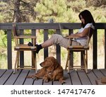 Woman Relaxing With Dog And...