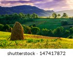 Stack of hay on the hillside under a menacing sky in the early morning - stock photo