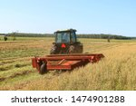 Small photo of Riversdale, Ontario / Canada - August 7, 2019 - Farmer cutting grain for silage driving a green tractor pulling a red hay bine