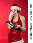 Small photo of Young woman in santa costume on a red background holding video cassette with a perplexed face. So-so gift outdated technology.