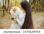 Stock photo charming young woman with little spitz dog in autumn park 1475639555