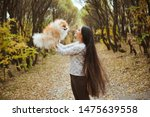 Stock photo charming young woman with little spitz dog in autumn park 1475639558
