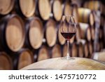 Closeup red wine glass on background of wooden oak barrels stacked in straight rows in order in cellar of winery, vault. Concept professional degustation, winelover, sommelier travel