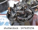 Empty boiled mussels in the pot on table, selective focus  - stock photo