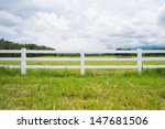 White Fence In Farm Field And...