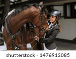 Girl Rider Adjusts Saddle On...