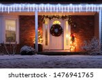 Beautiful winter blizzard night. House main entrance and porch decorated with glowing lights for winter holidays. Night scene with fresh snow. Christmas and New Year holiday background.