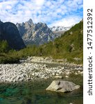 Small photo of Alpine landscape with mountains overtop a river valley on a sunny day