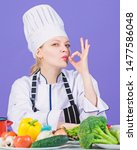 Small photo of The best foods for every vitamin and mineral. Professional cook gesturing ok. Pretty woman chef with vitamin vegetables on table. Kitchen maid preparing vitamin food. Getting vitamin the natural way.