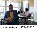 Small photo of Front view cloe up of young African American businessman sitting using tablet computer in an office. A Caucasian businessman and an African American businesswoman work sitting at a desk in the