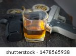 Glass of whiskey and gun.the...