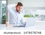 Small photo of Handsome man working using computer laptop and drinking a cup of coffee stressed with hand on head, shocked with shame and surprise face, angry and frustrated. Fear and upset for mistake.