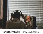 Small photo of Special agent listens on the reel tape recorder. Officer wiretapping in headphones. KGB spying of conversations.
