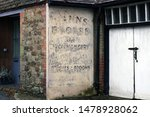 Small photo of worn old vintage painted ironmonger sign on brick wall