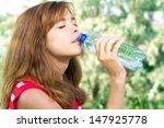 beautiful girl drinks water... | Shutterstock . vector #147925778