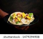 Small photo of Restaurant dish with papadum, crab, gamba, apple and mango, dark background