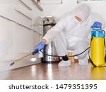 a professional pest control contractor or exterminator at work with chemicals in the kitchen in his typical work wear in his fight against pests bugs and mold. squads on the parquet and spray chemical