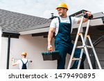 Small photo of selective focus of happy workman standing on ladder with toolbox near coworker