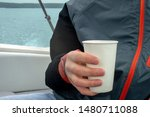 Man Holds A Paper Glass Sittin...