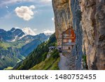 Swiss Alps and a mountain restaurant under the Ascher cliff viewed from mountain Ebenalp in the Appenzell region in Switzerland