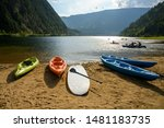 Summer scene of Three Valley Lake with kayaks, canoes, and other recreational watercrafts lying on the sandy beach while some people are kayaking, canoeing on the lake, British Columbia, Canada