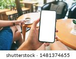 Small photo of Mockup image of a man's hand holding black mobile phone with blank white screen with woman drinking coffee in cafe