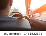 Small photo of Back side of man driving on the road holding steering wheel steady using low gear and slow speed to avoid accidents. Transportation, safety, driving carefully, lifestyle and traffic concept