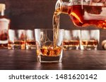 Small photo of A glass of whiskey on a wooden table in which poured whiskey from a bottle. In the background are four glasses of whiskey, a full bottle of whiskey and a wooden bottle stopper.