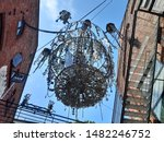 Small photo of Oslo, Norway – July 17, 2019: Artistic chandelier of fussed glass hanging in street at Oslo Bla, Grunerlokka district.
