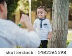 Small photo of Baby boy puff up soap bubbles with his father in the garden. Family portret concept.