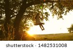 Small photo of child rides a rope swing on an oak branch in forest. girl laughs, rejoices. young girl swinging on swing under a tree in sun, playing with children. close-up. Family fun in park, in nature.
