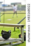 Softball helmets left unattended on the aluminium seating waiting for a next hitter picking up for a next play while seeing defensive team in action in a girl high school game during a summer time.