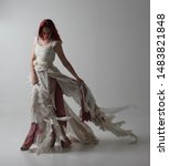 Small photo of full length portrait of red haired girl wearing torn and tattered wedding dress. Standing pose against a studio background with contrasty shadow lighting.