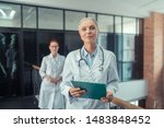 Doctor with a stethoscope. Calm senior female doctor with a stethoscope around her neck standing in the corridor next to her young colleague - stock photo