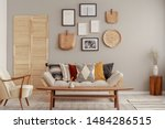 Wooden and wicker accessories in fashionable scandinavian living room interior with futon sofa with pillows